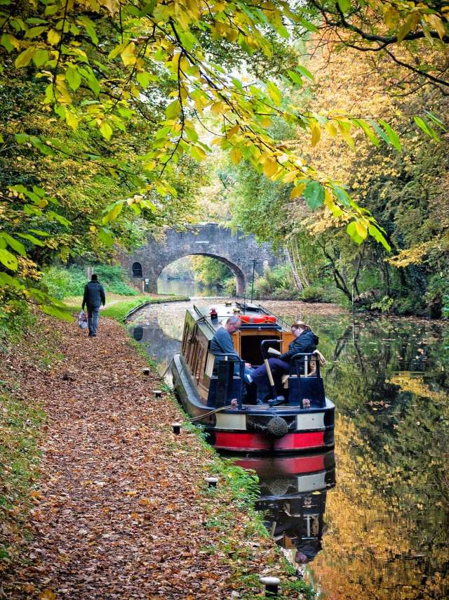 A couple on a hire boat enjoying the peace and quiet of Curdworth cutting on the Birmingham and Fazeley Canal