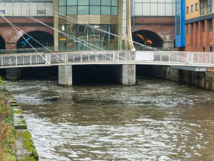 The fast flowing River Aire running below the railway station